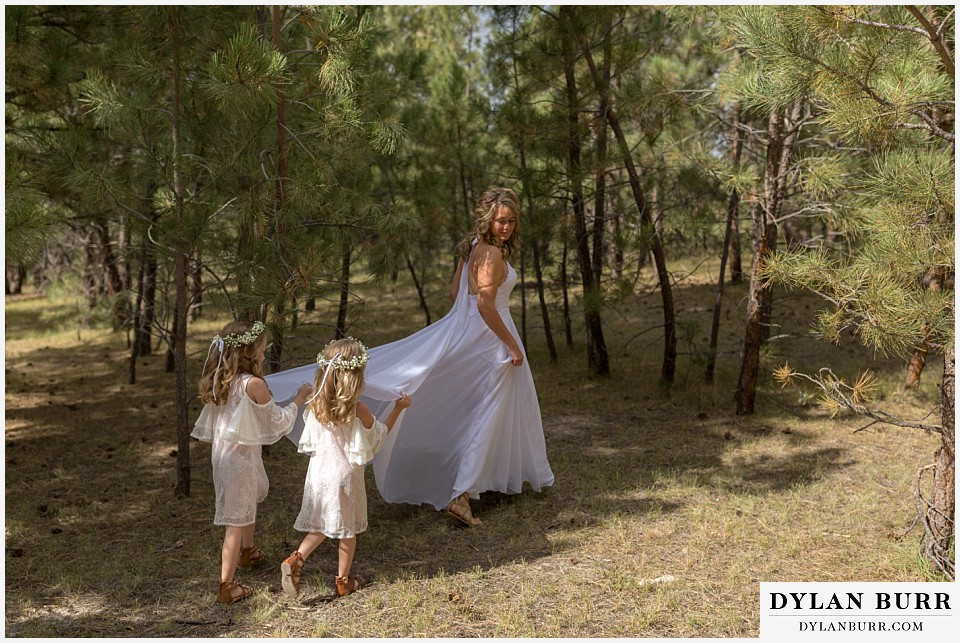 boho backyard colorado wedding bride walking in forest with daughters holding dress