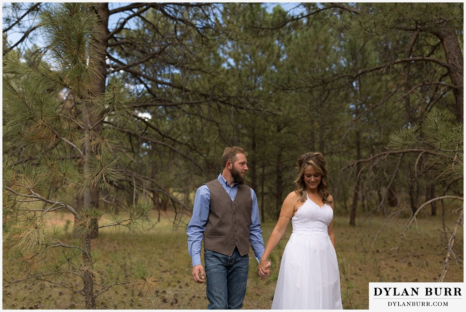 boho backyard colorado wedding bride and groom walking in forest holding hands