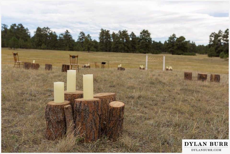 boho backyard colorado wedding ceremony site with tree stumps and candles