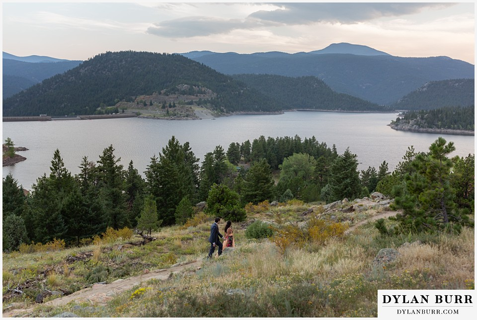 boulder colorado engagement session in the mountains wide view of mountains and couple walking to the lake