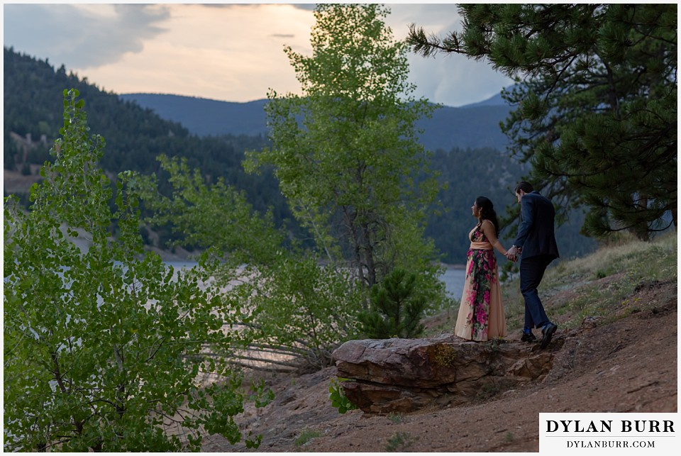 boulder colorado engagement session in the mountains couple standing on rock at sunset by the lake
