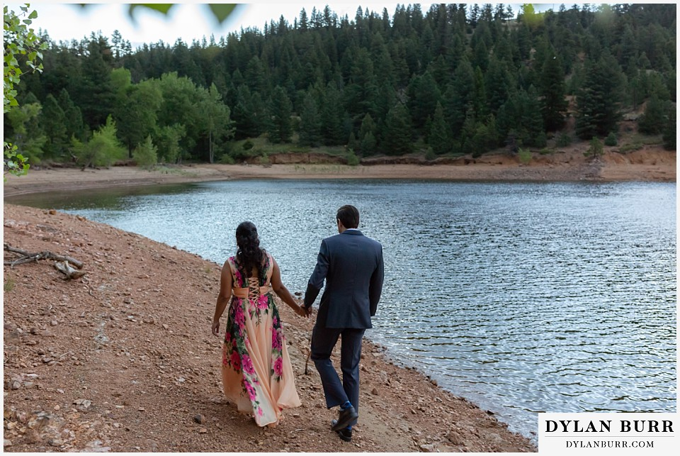 boulder colorado engagement session in the mountains couple walking together along the lake