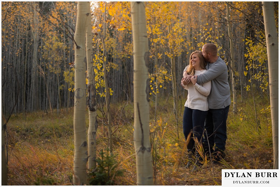 colorado mountain engagement session having a snuggle in the trees
