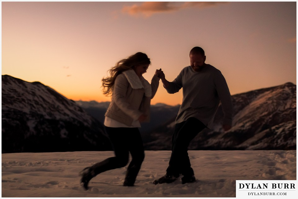 colorado mountain engagement session running in snow on the top of a mountain pass