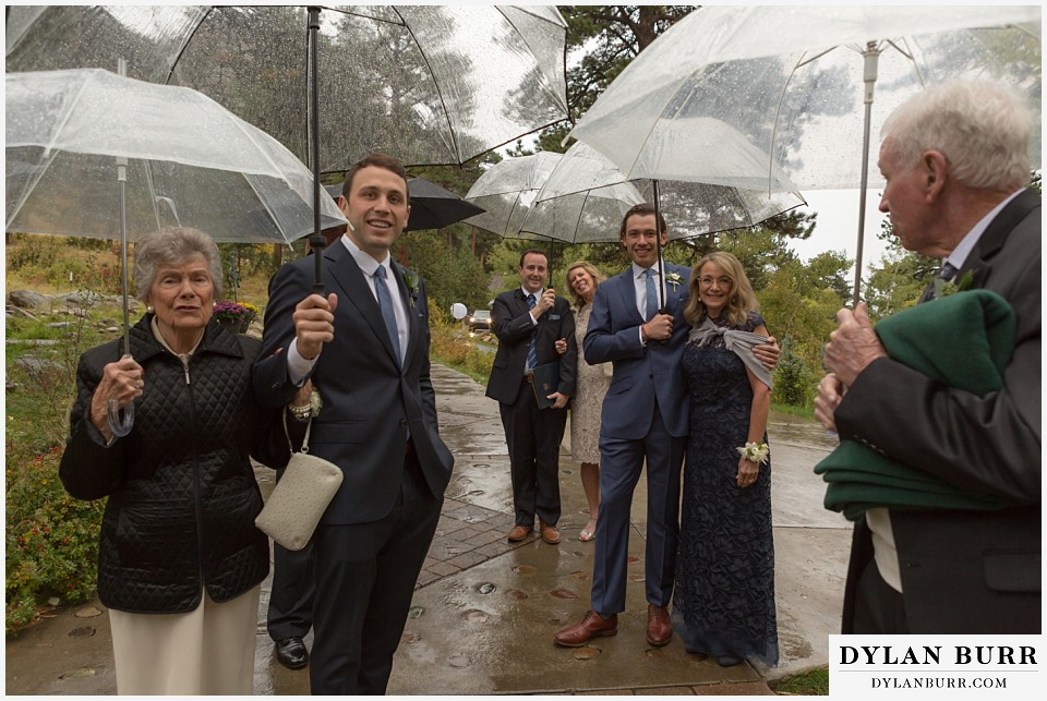 della terra wedding estes park colorado mountain wedding family with umbrellas at rainy ceremony site