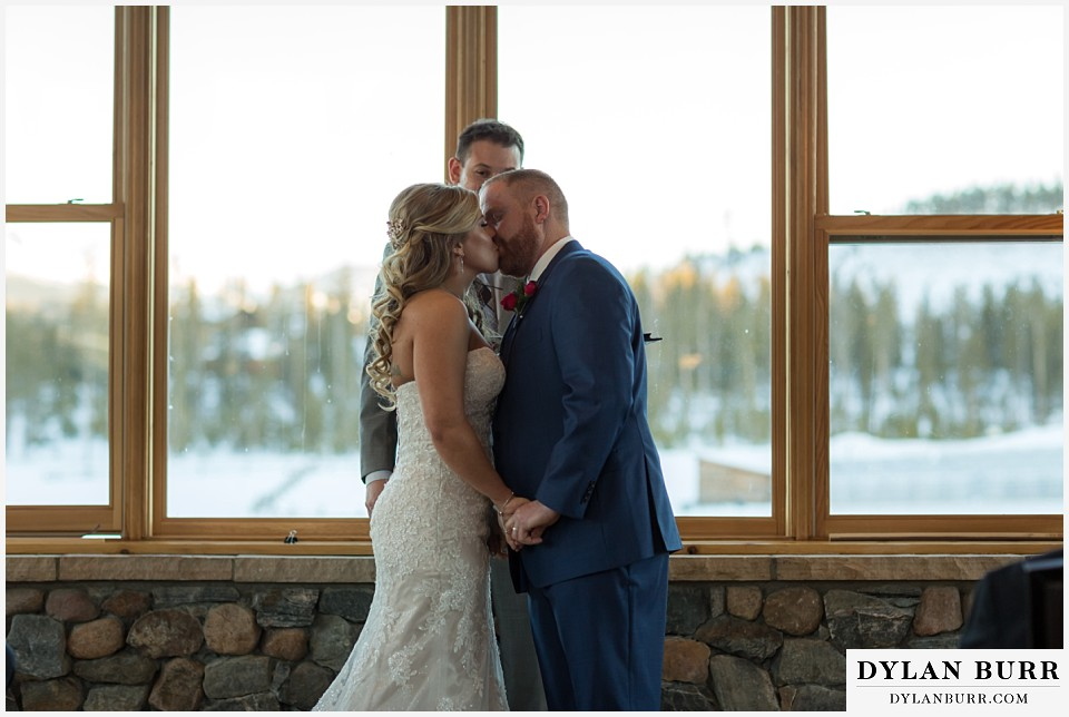 devils thumb ranch wedding in winter ceremony timber house first kiss