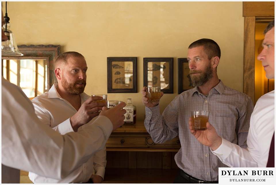 devils thumb ranch wedding in winter groomsmen whiskey toast