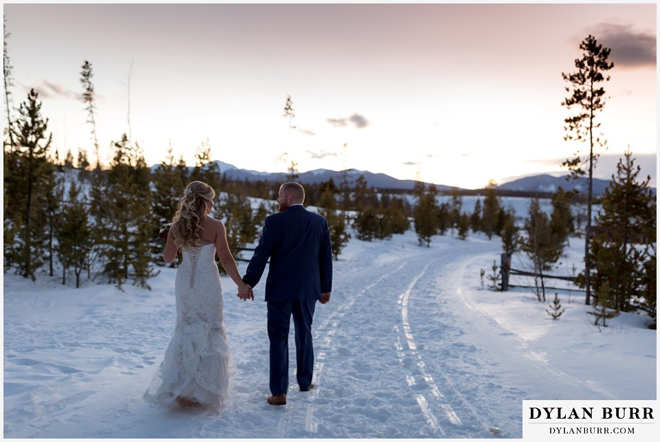 devils thumb ranch wedding in winter newlyweds holding hands