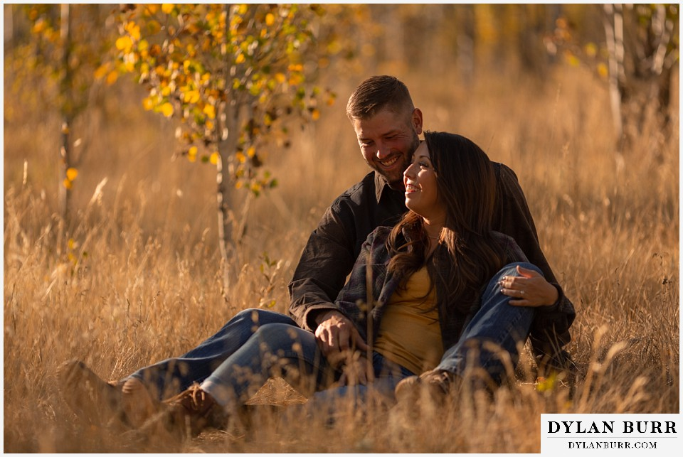 engagement photos golden colorado photographer couple laughing together in tall grass