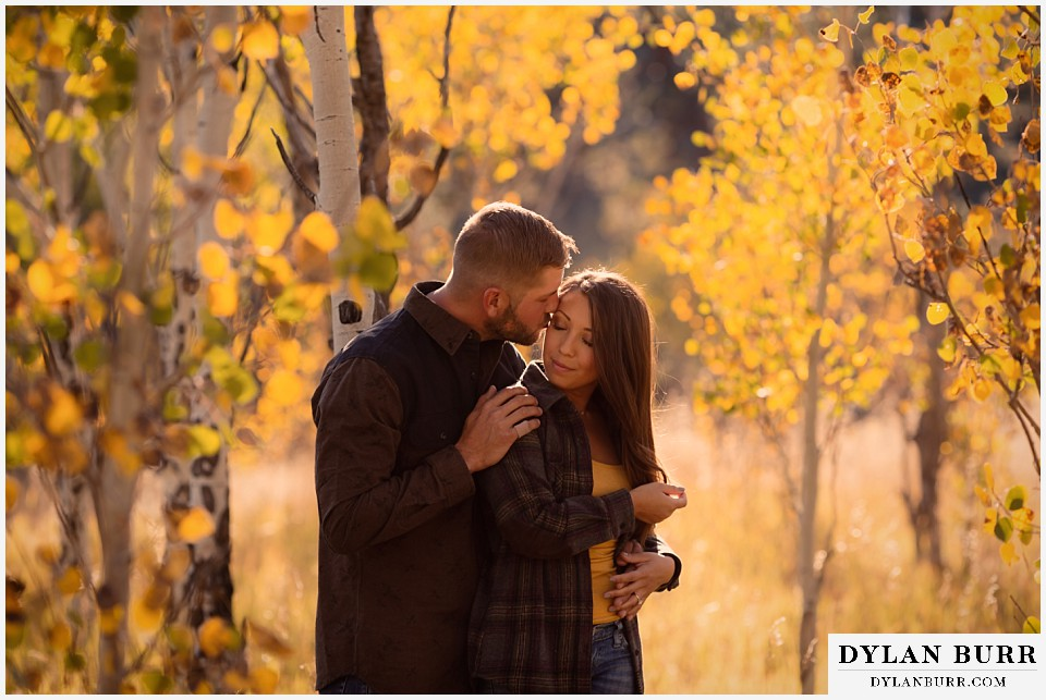 engagement photos golden colorado photographer couple giving cheek kisses