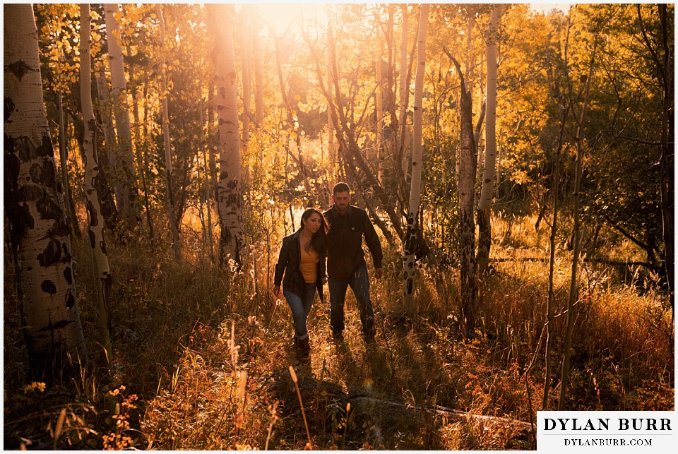 engagement photos golden colorado photographer couple walking out of aspen forest
