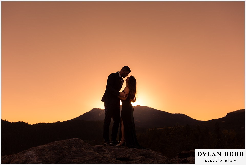 engagement photos golden colorado photographer couple standing on top of mountain at sunset