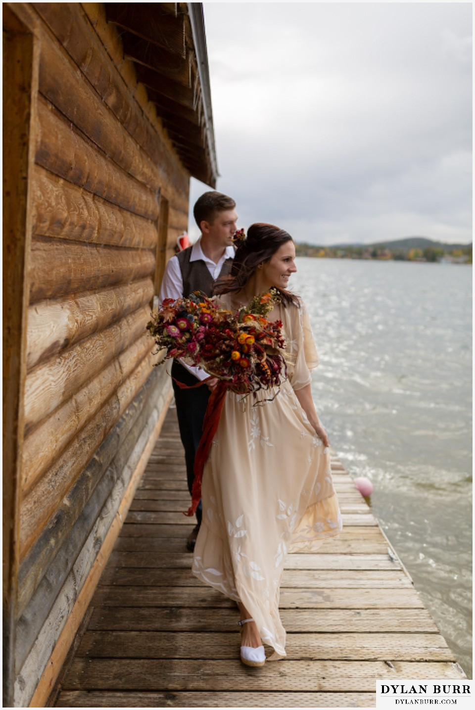 grand lake wedding elopement bride and groom walking back to shore from boat house