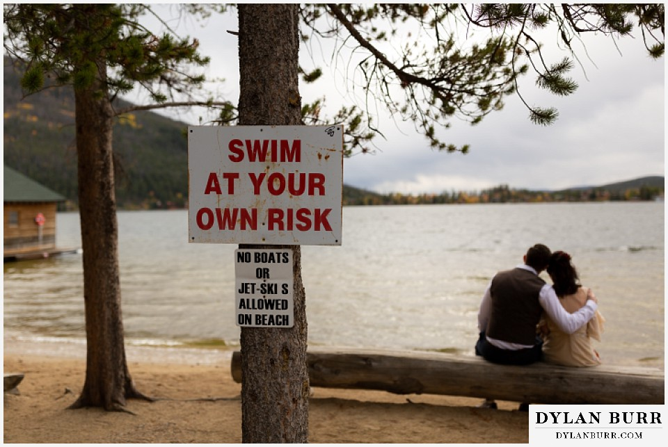 grand lake wedding elopement bride and groom on bench with swim at your own risk sign