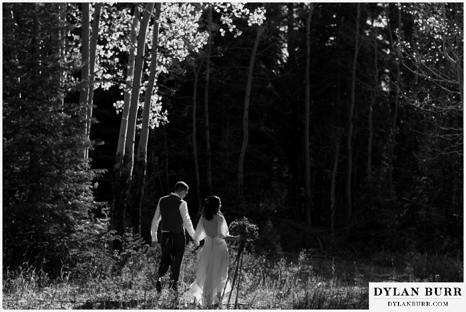 rocky mountain national park grand lake wedding elopement black and white of groom and bride walking into forest