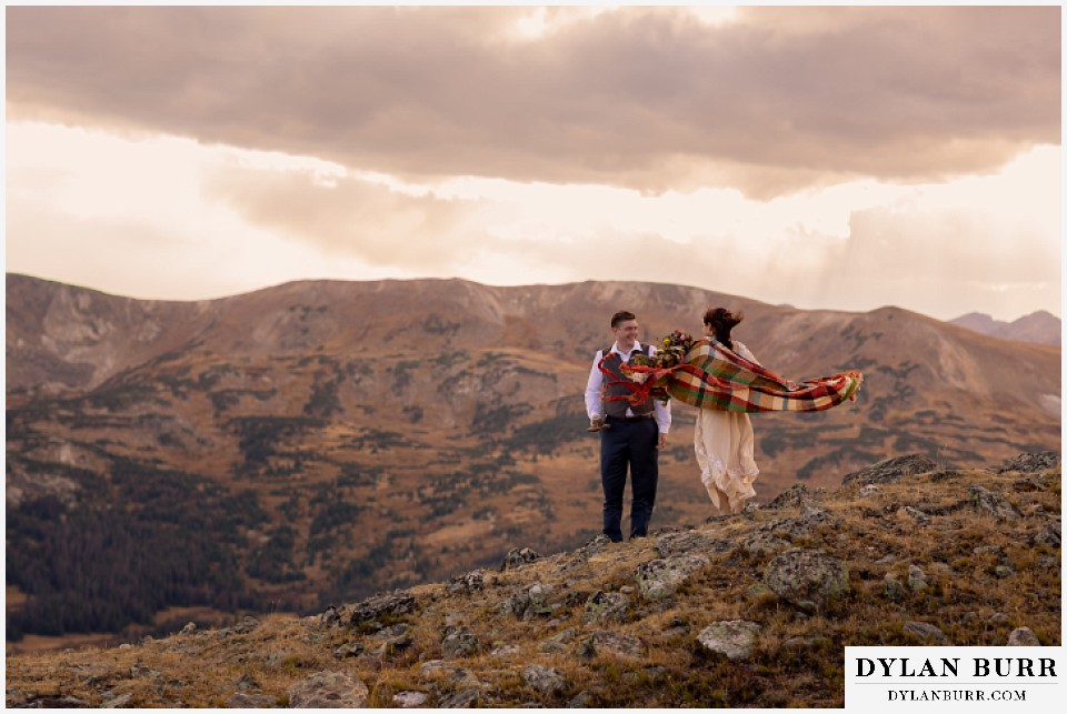 rocky mountain national park grand lake wedding elopement groom and bride with blanket blowing in the wind