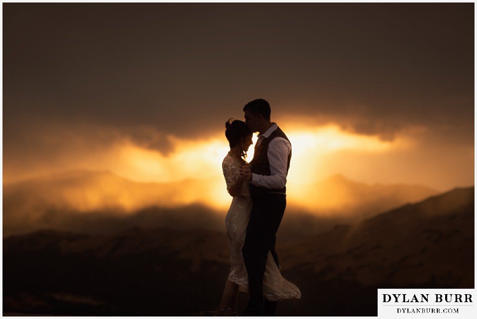 rocky mountain national park grand lake wedding elopement bride and groom dancing on mountaintop at sunset