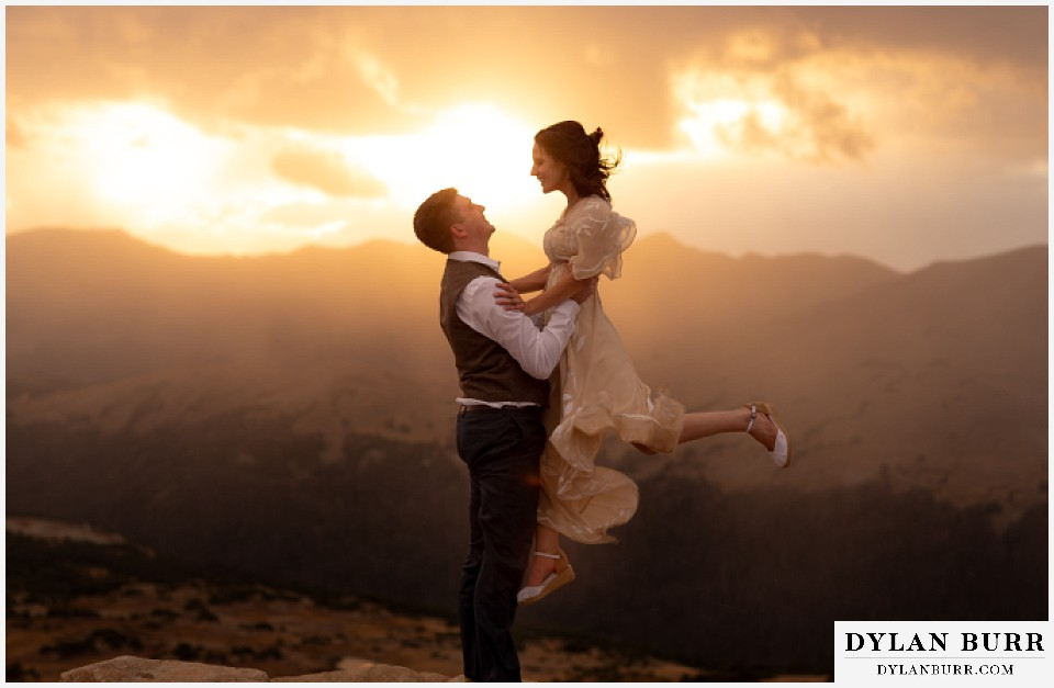 rocky mountain national park grand lake wedding elopement groom lifting up bride in air at sunset
