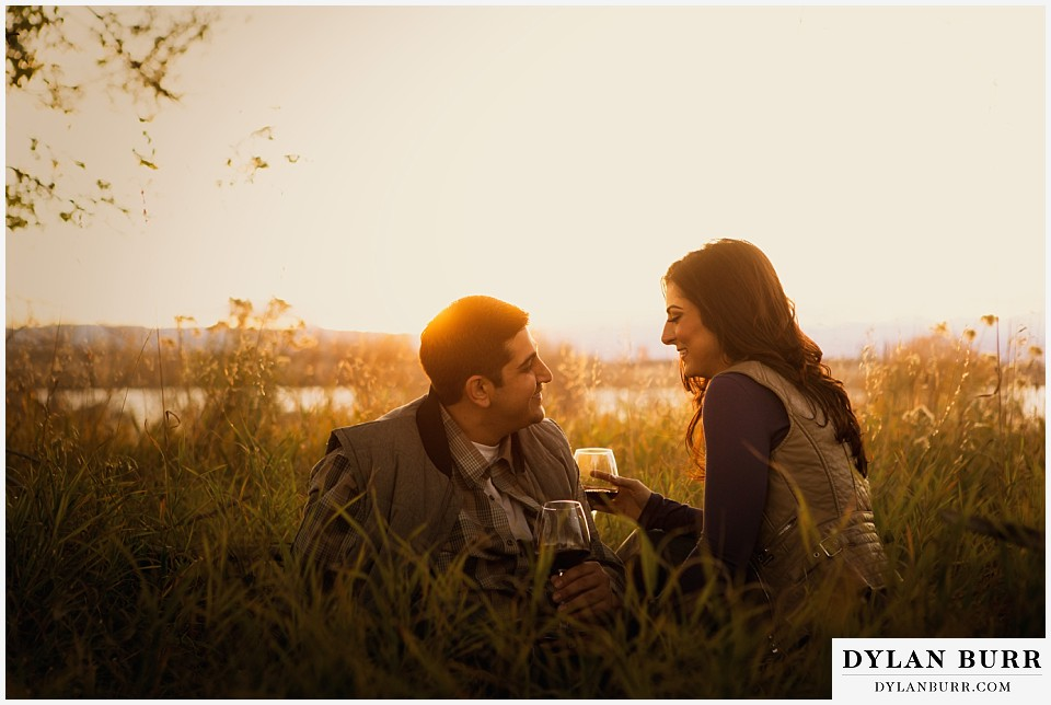 how to prepare for my engagement session couple drinking wine in field