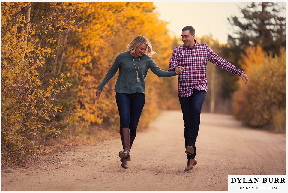 how to prepare for my engagement session couple skipping down road in fall colors