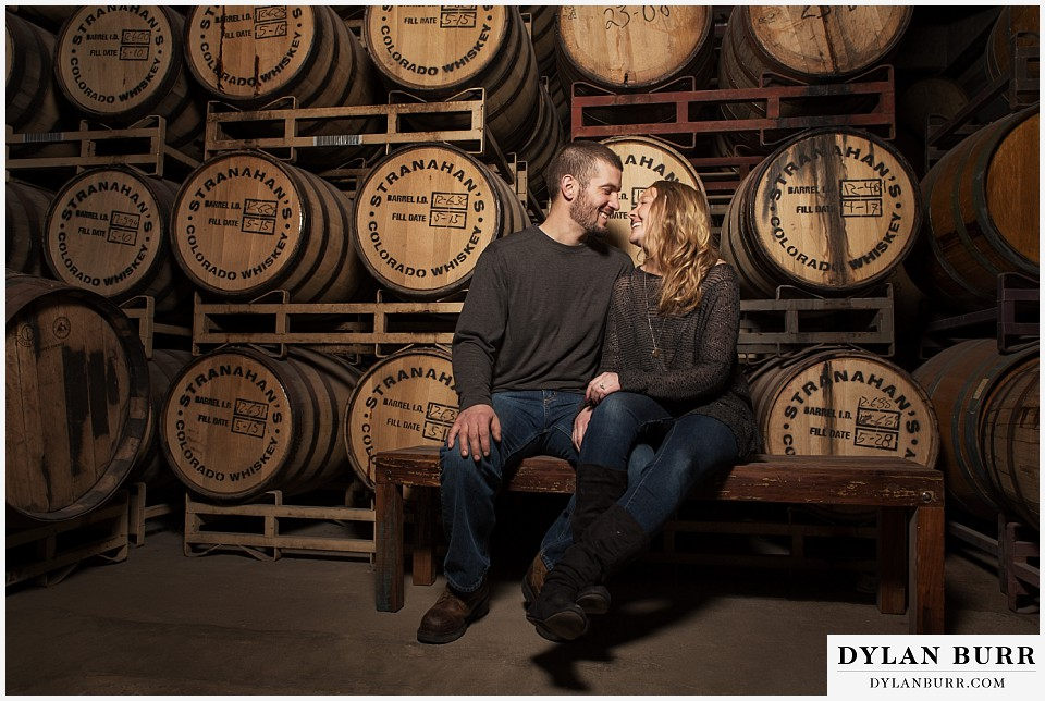 how to prepare for my engagement session couple stranahans whiskey tour near wall of barrels