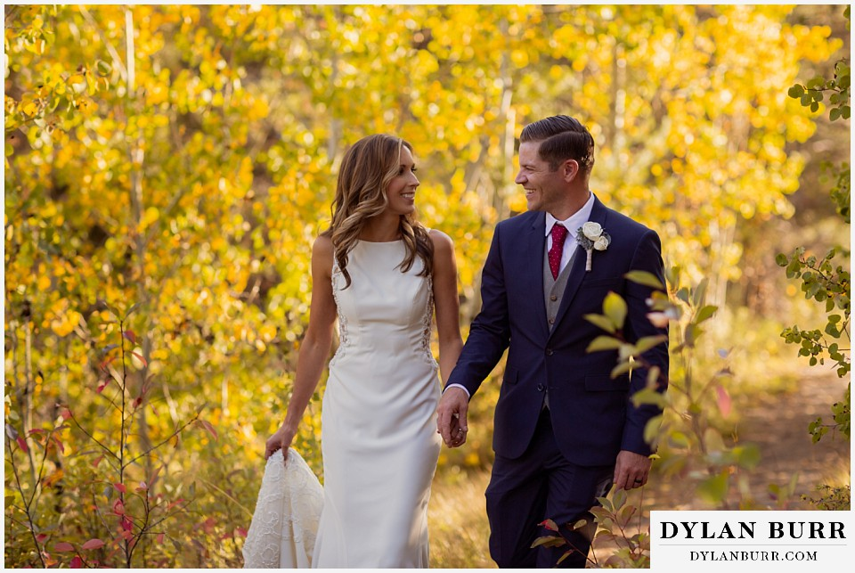 jackson lake lodge wedding grand tetons wyoming bride and groom walking in forest in the fall