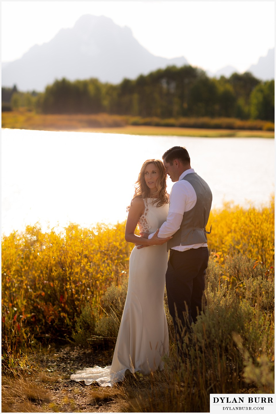 jackson lake lodge wedding grand tetons wyoming bride and groom in the fall by the snake river and mt moran