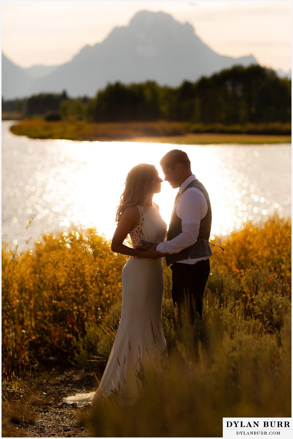 jackson lake lodge wedding grand tetons wyoming bride and groom standing in sunlight with mt moran in background