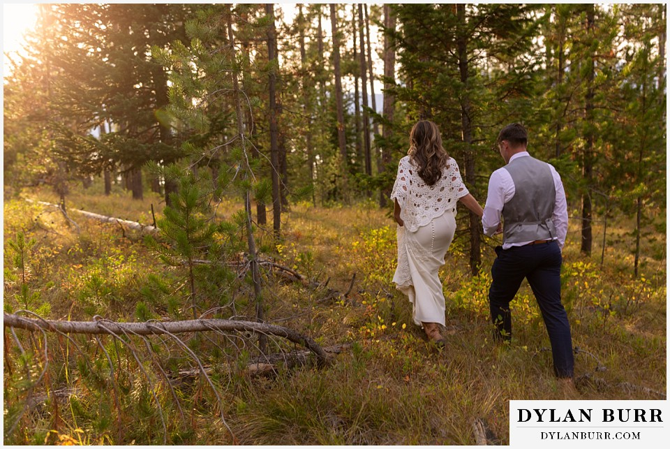 jackson lake lodge wedding grand tetons wyoming bride and groom walking into forest at sunset