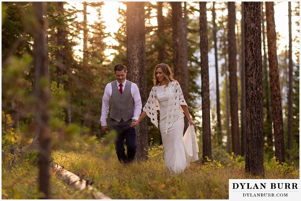 jackson lake lodge wedding grand tetons wyoming bride and groom walking in pine tree forest