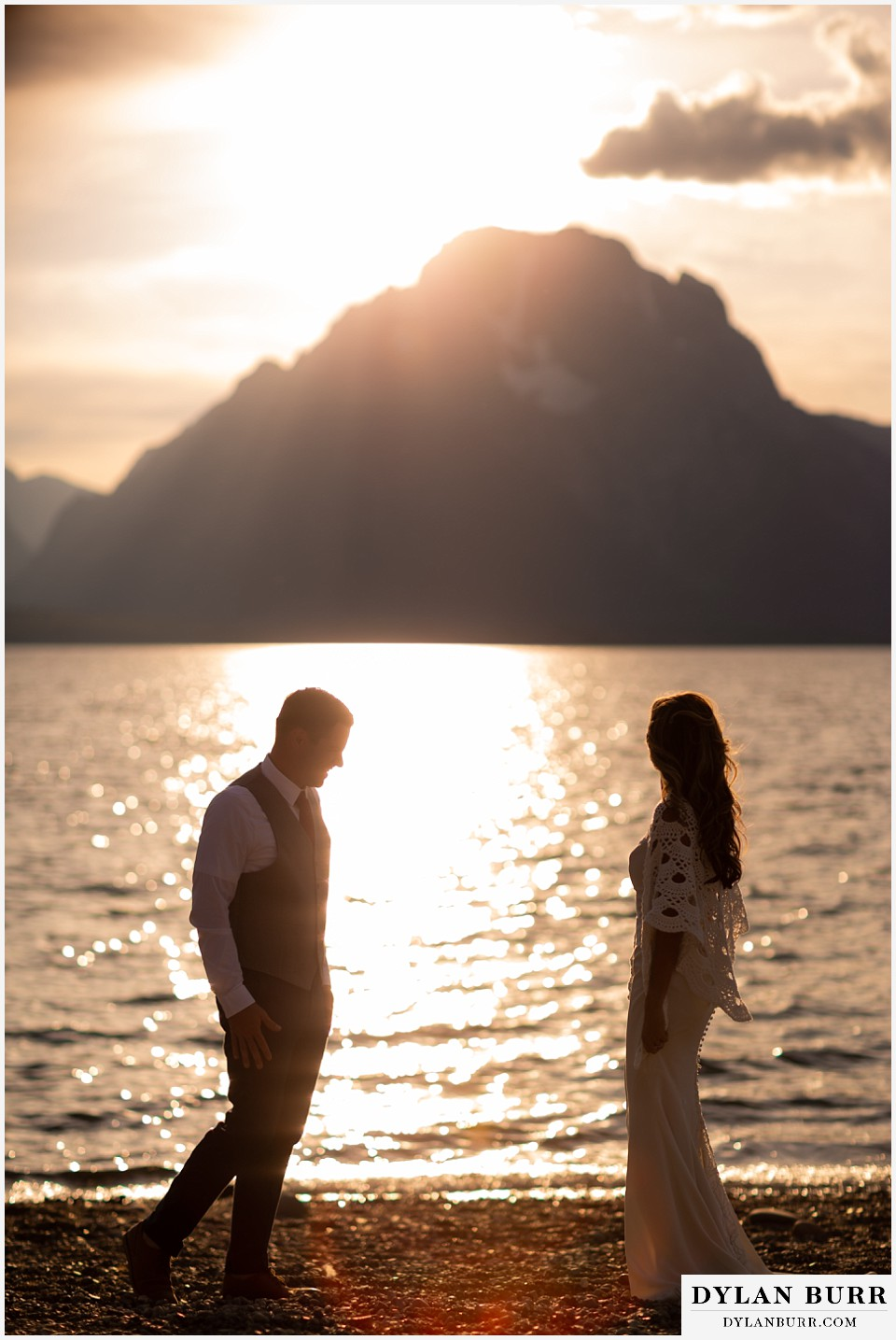jackson lake lodge wedding grand tetons wyoming bride and groom walking in sunlight by the lake and mt moran