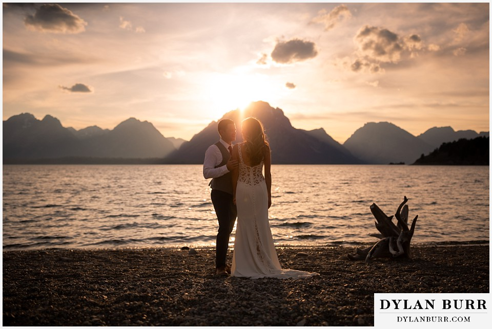 jackson lake lodge wedding grand tetons wyoming bride and groom at jackson lake at sunset with mountains in the background