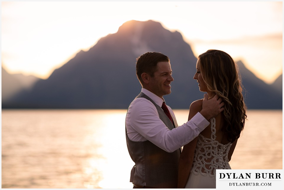 jackson lake lodge wedding grand tetons wyoming loving groom reaching out for his wife at sunset