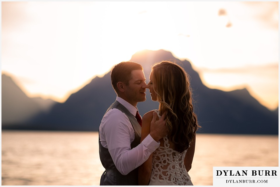 jackson lake lodge wedding grand tetons wyoming bride and groom going in for a kiss at sunset near Jackson lake