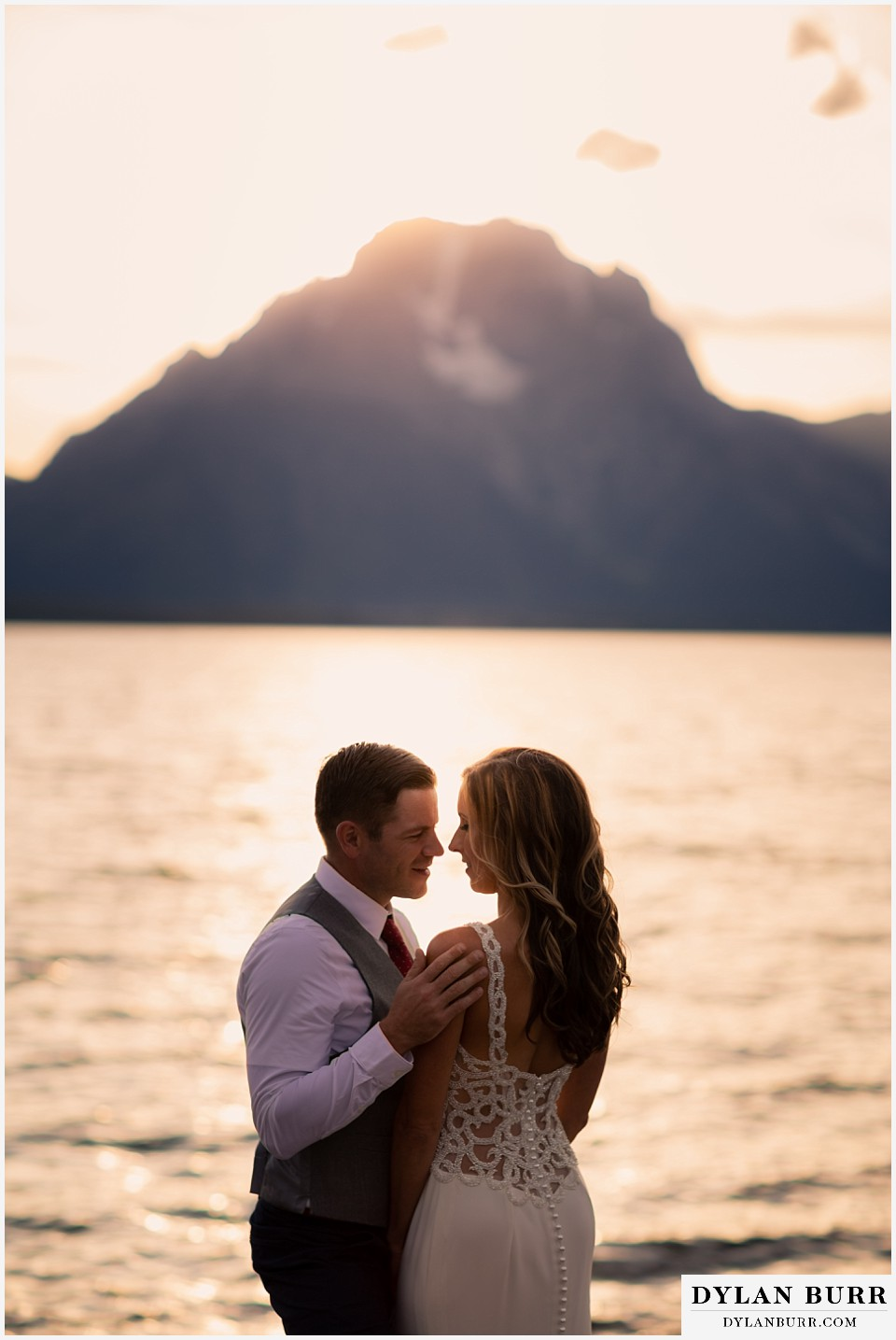 jackson lake lodge wedding grand tetons wyoming groom looking sweetly at his wife at sunset with mt mornan in background
