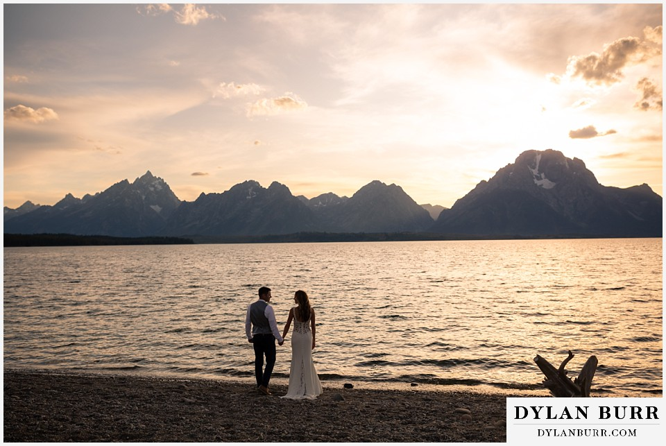 jackson lake lodge wedding grand tetons wyoming bride and groom at sunset with grand teton and mt moran in background