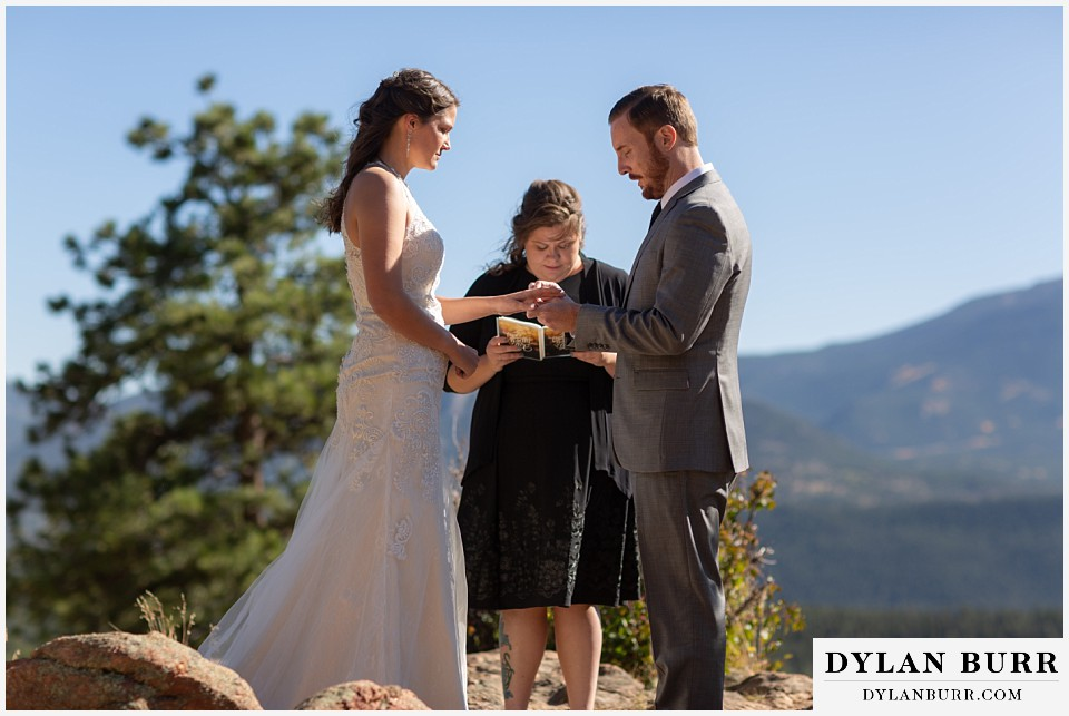 rocky mountain national park elopement wedding groom placing ring on brides finger