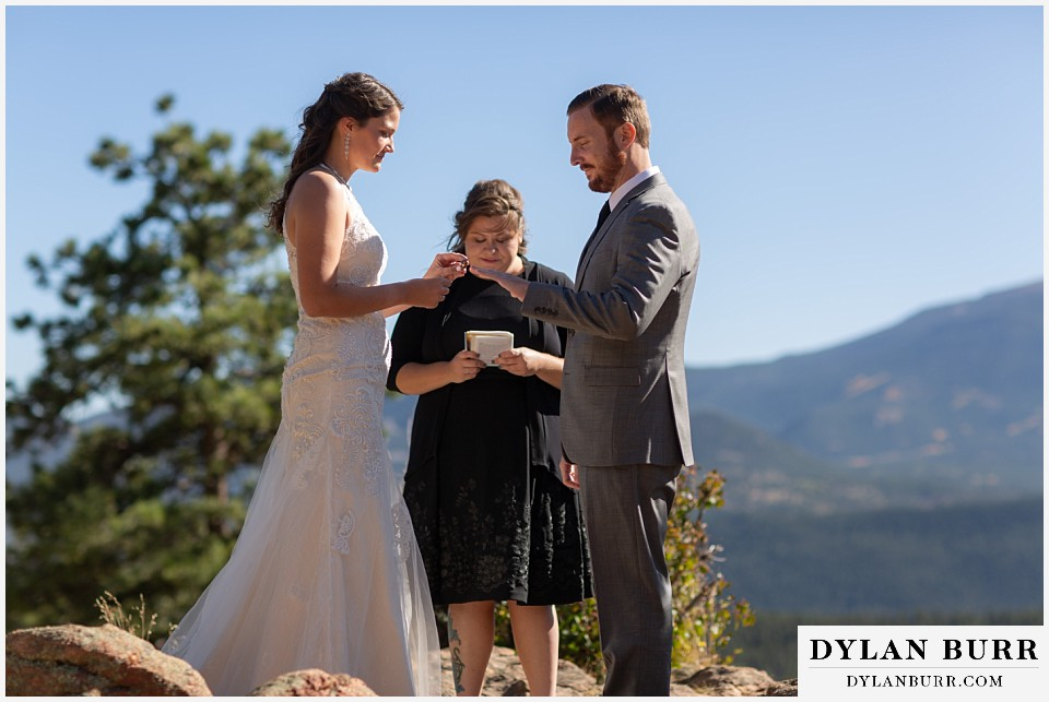 rocky mountain national park elopement wedding bride placing ring on grooms finger