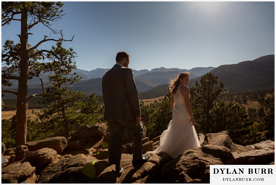 rocky mountain national park elopement wedding bride and groom walking in sunlight on mountain top