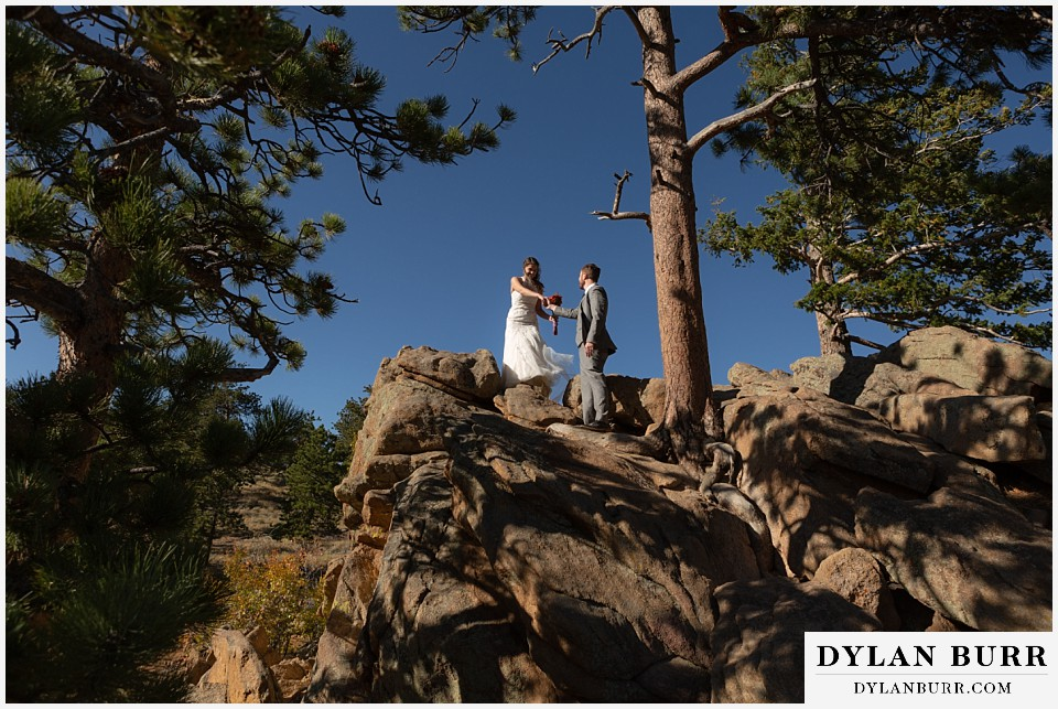 rocky mountain national park elopement wedding bride and groom hiking down mountain