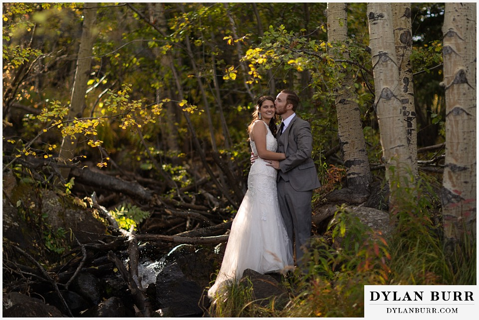rocky mountain national park elopement wedding bride and groom near river in aspen forest