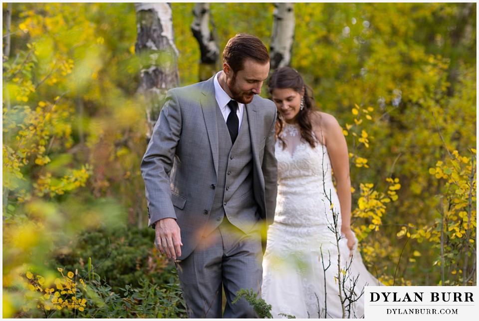 rocky mountain national park elopement wedding groom leading bride in aspen forest