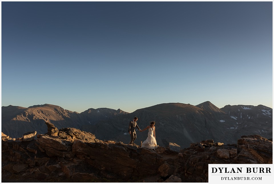 rocky mountain national park elopement wedding bride and groom walking along high mountain ridge