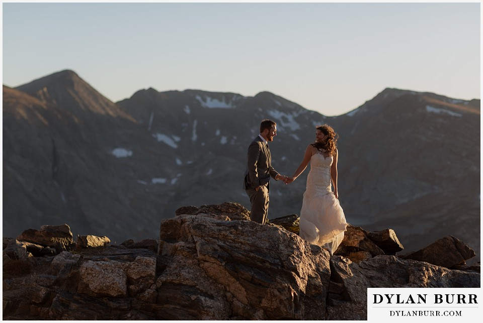 rocky mountain national park elopement wedding bride looking back at groom on mountain ridge