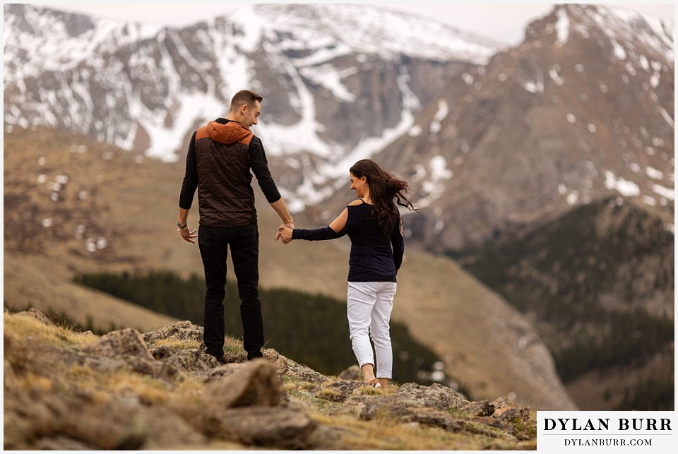 rocky mountain engagement session in colorado hiking with snowy mountains