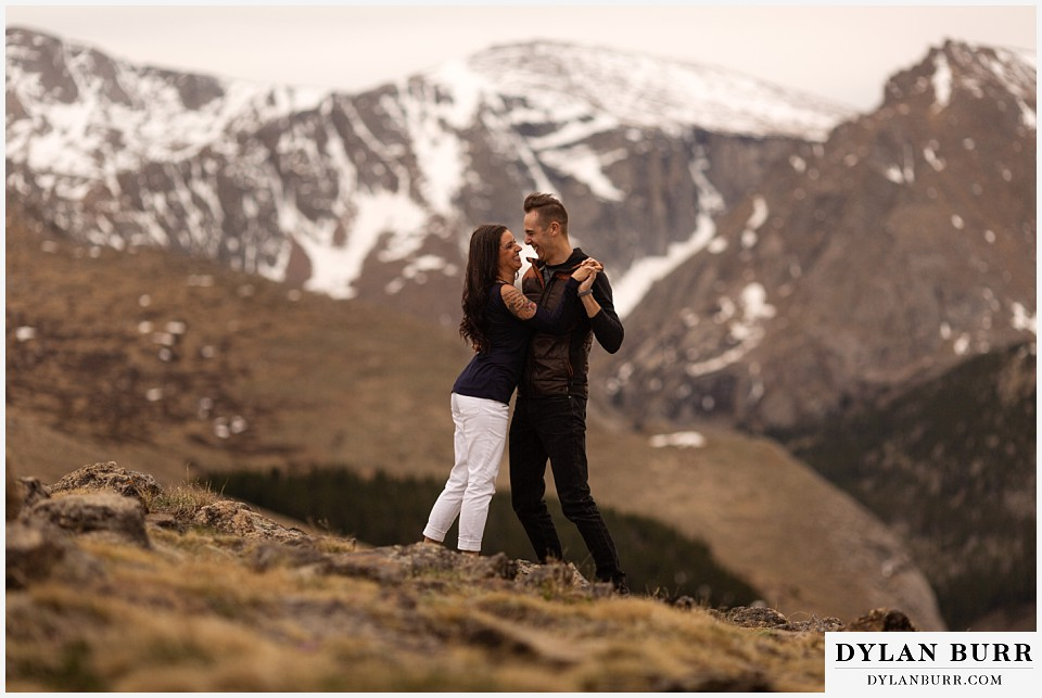 rocky mountain engagement session in colorado dancing with snow on mountains in background