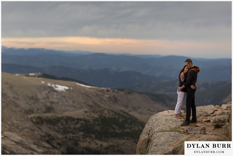 rocky mountain engagement session in colorado hugs on a mountain ledge