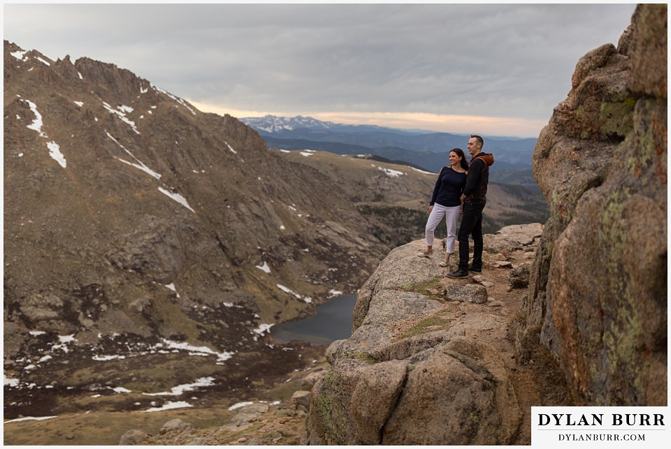 rocky mountain engagement session in colorado looking out over the mountain valley and lakes below