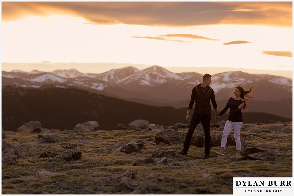 rocky mountain engagement session in colorado couple walking together with hair blowing in the wind on top of a mountain