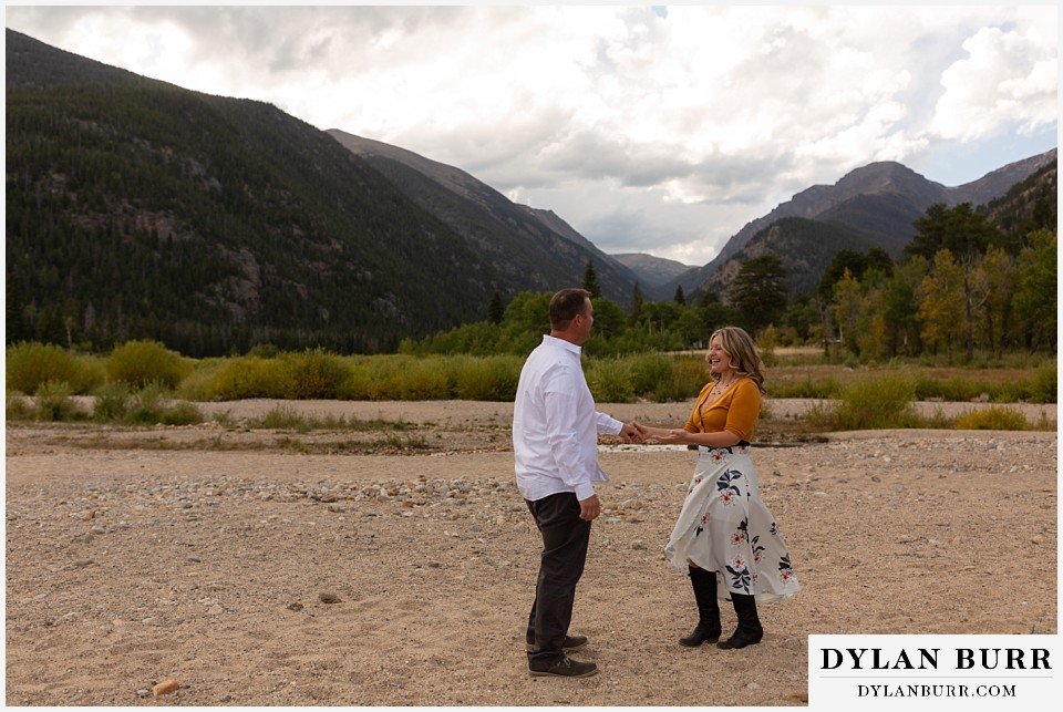 rocky mountain national park elopement wedding bride and groom dancing together near river